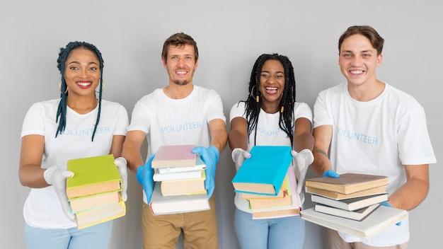 Pessoas sorridentes segurando um monte de livros para doá-los
