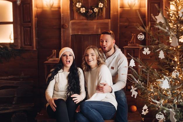Pessoas sorridentes sentadas na varanda de madeira em frente à porta com a coroa de natal