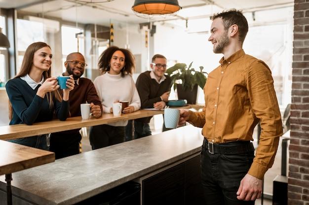 Pessoas sorridentes tomando café durante uma reunião