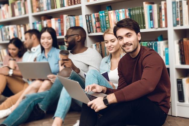 Pessoas sorrindo e conversando perto de estante na biblioteca.