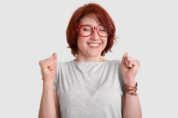 Pessoas, sucesso, conceito de celebração. mulher ruiva muito feliz com cabelo curto, cerra os punhos, tem um sorriso terno, vestido casualmente, modelos na parede branca do estúdio, expressa emoções positivas