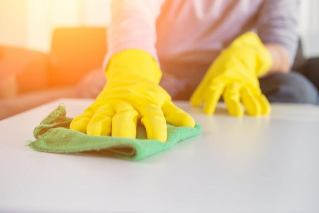 Pessoas, tarefas domésticas e conceito de arrumação - close up of man hands cleaning table with cloth in home Foto gratuita