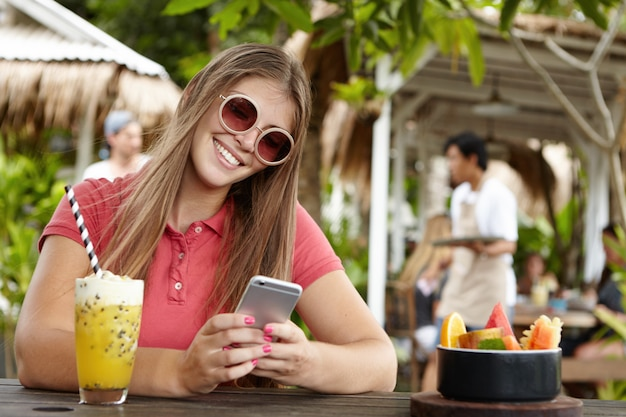 Pessoas, tecnologia moderna e conceito de comunicação. menina bonita em tons da moda mandando mensagens de texto para amigos, verificando o feed de notícias nas redes sociais enquanto navega na internet em um café