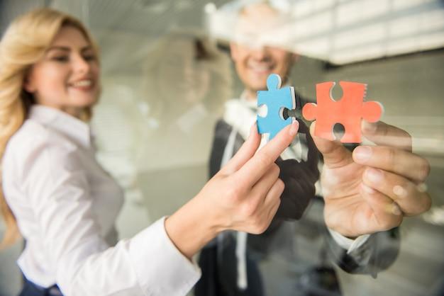 Pessoas tentando conectar pequenos pedaços de quebra-cabeça no escritório.