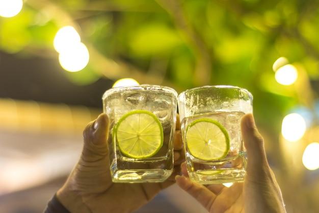 Pessoas tilintando com gin tonic e limão fatiado em copos.