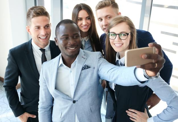 Pessoas tirando selfie em reunião de negócios