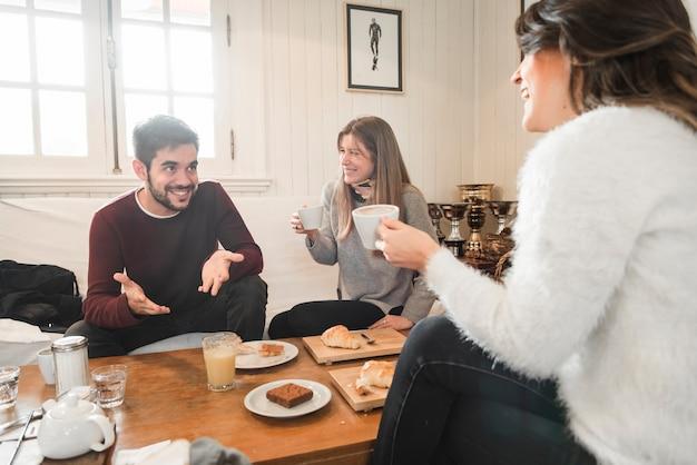 Pessoas tomando café e conversando em casa