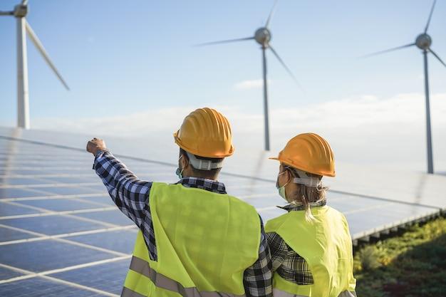 Pessoas trabalhando para fazenda de energia alternativa - processo de geradores de energia eólica e painéis solares