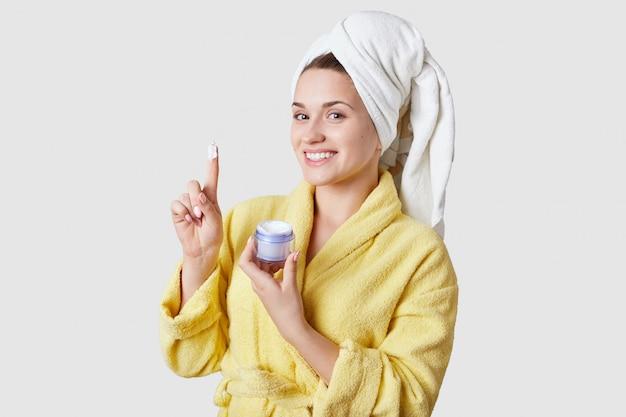 Pessoas, tratamento facial e conceito de cosmetologia. a jovem mulher bonita saudável com sorriso, usa o creme para a pele, veste a roupa doméstica após o banho, modelos no estúdio branco.