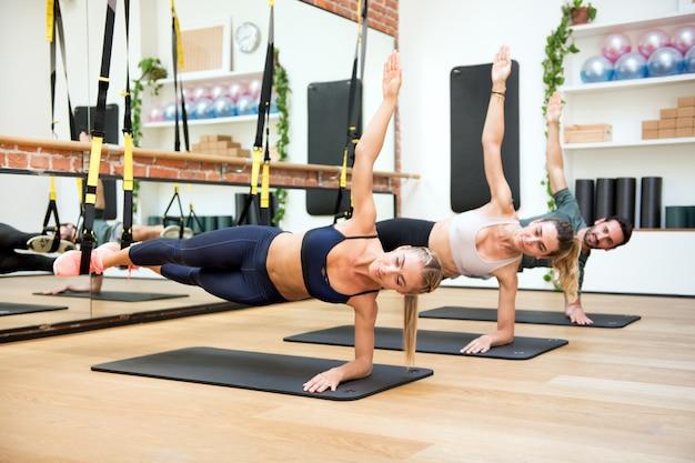 Pessoas treinando cotovelos laterais com trx no ginásio