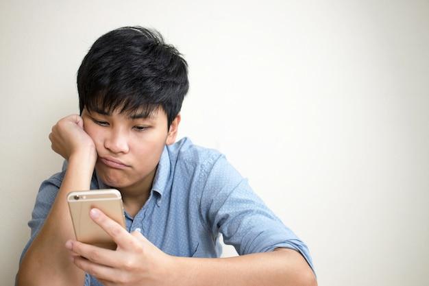 Pessoas tristes estão verificando o e-mail em seus telefones celulares no quarto.