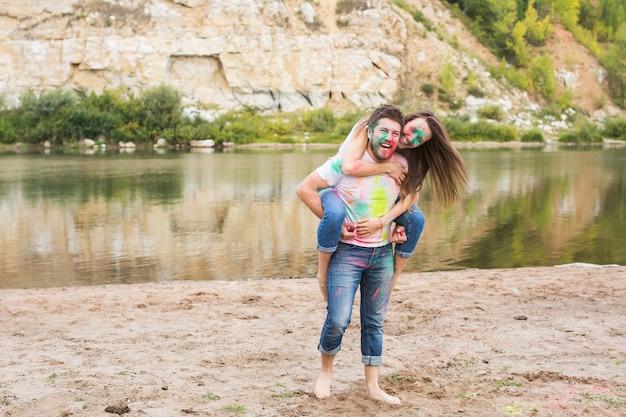 Pessoas, turismo de verão e conceito de natureza - jovem mulher atraente sentada nas costas do namorado na natureza