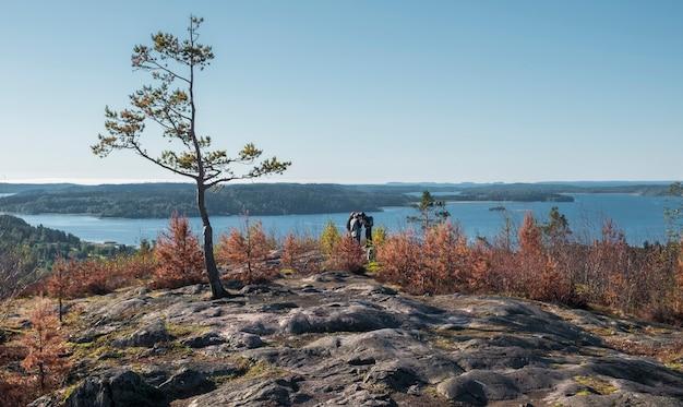 Pessoas, turistas no topo do monte hiidenvuori, na carélia, perto do lago ladoga, no outono em um dia ensolarado