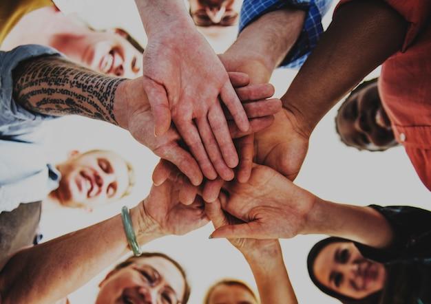 Pessoas unindo as mãos e sorrindo