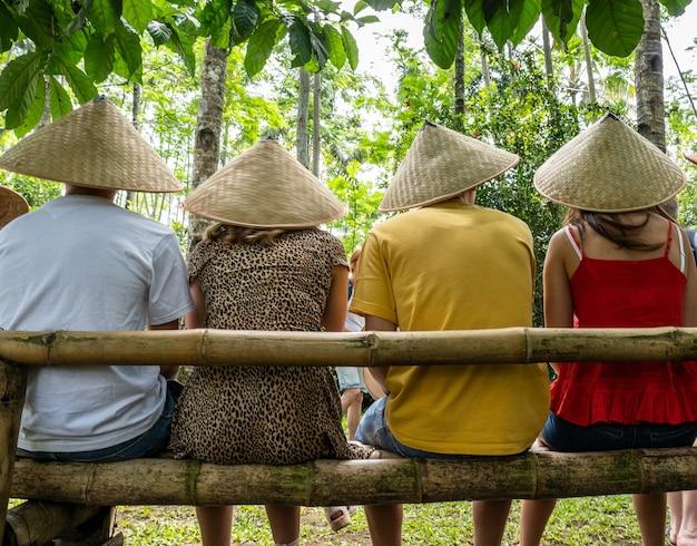 Pessoas usando chapéus cônicos asiáticos sentadas em um banco de bambu