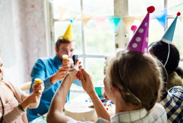 Pessoas usando festa popper em uma festa de aniversário