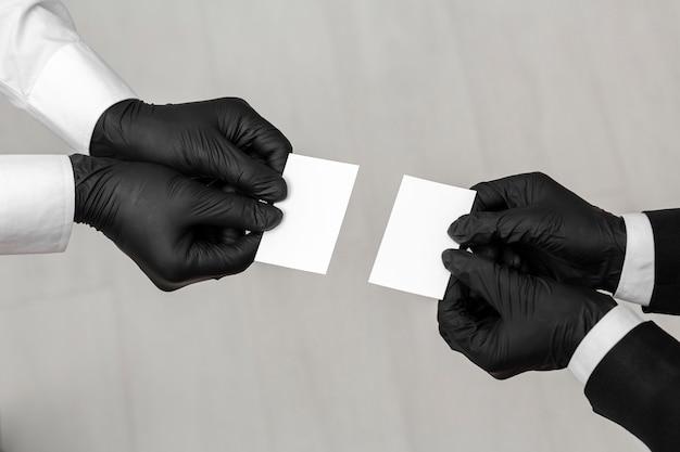 Pessoas usando luvas pretas segurando cartões de visita