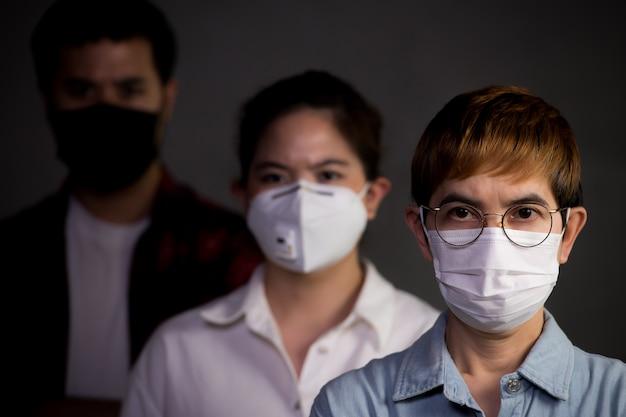 Pessoas usando máscaras cirúrgicas parecendo preocupadas com a situação de um surto de pandemia