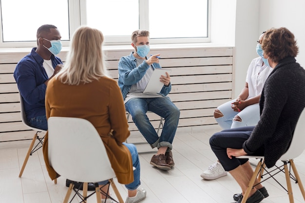 Pessoas usando máscaras médicas na reunião
