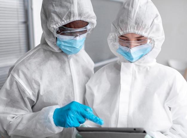 Pessoas usando roupas de proteção em uma área de risco biológico