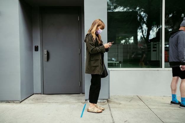 Pessoas usando seus telefones e tendo distanciamento social enquanto fazem fila durante a pandemia de coronavírus