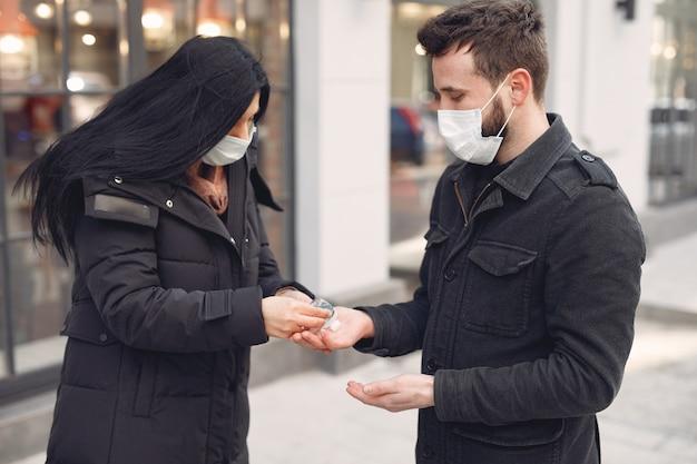 Pessoas usando uma máscara protetora em pé na rua enquanto estiver usando gel de álcool