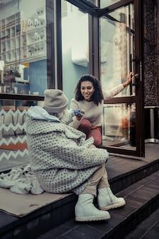 Pessoas úteis. jovem alegre ajudando uma senhora idosa e sendo amigável com as pessoas