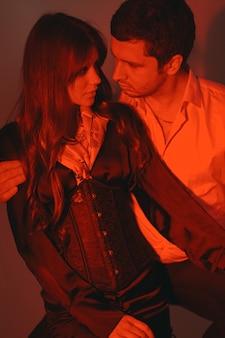 Pessoas vestidas com roupas clássicas. casal elegante em um momento sensual na parede branca.