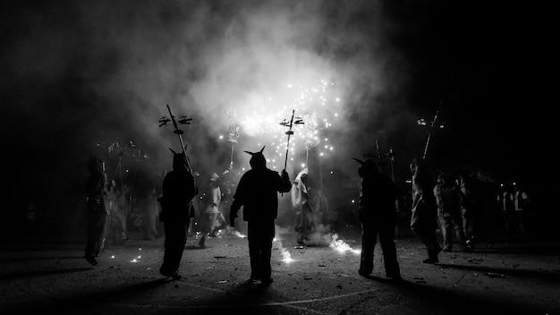 Pessoas vestidas como demônios comemorando com pirotecnia