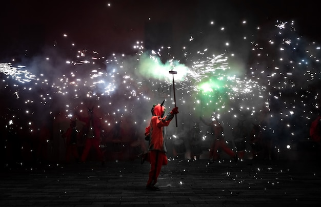 Pessoas vestidas como demônios dançando com fogos de artifício
