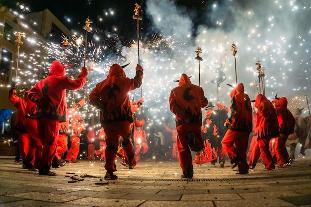 Pessoas vestidas como demônios fazendo uma performance com pirotecnia