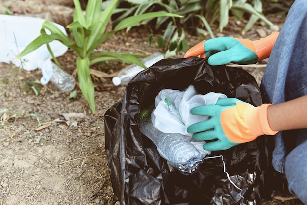 Pessoas voluntárias ajudando a manter a natureza limpa e recolhendo o lixo