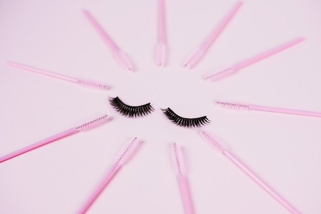 Pestanas de fita preta falsa e escovas para pentear cílios de extensão em um fundo pastel na moda rosa. cílios postiços, aplicador e pincéis. vista superior, plana