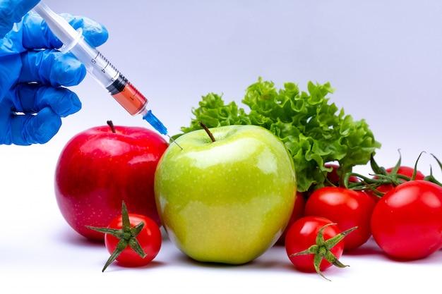 Pesticidas e nitratos são injetados em vegetais e frutas com uma seringa. conceito de ogm e organismo geneticamente modificado. produtos saudáveis naturais e sem ogm, sem aditivos químicos.