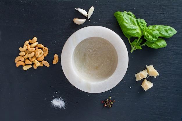 Pesto e ingredientes no fundo de pedra escura