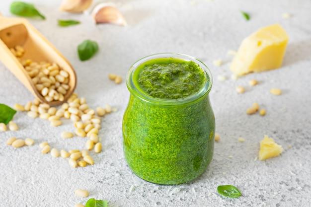 Pesto verde em uma jarra de vidro feita de folhas frescas de manjericão, pinhões, parmesão, alho e olia em um fundo claro.