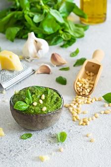 Pesto verde em uma tigela feita de folhas frescas de manjericão, pinhões, parmesão, alho e olia em um fundo claro.