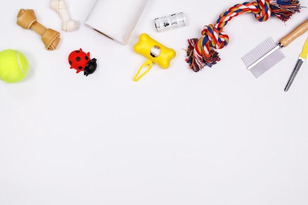 Pet acessórios, comida e brinquedo em fundo branco. lay plana. vista do topo.