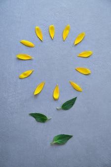 Pétalas amarelas colocadas em uma forma circular simulando uma flor com folhas verdes no centro da imagem de cima em um fundo listrado de textura cinza com luz natural