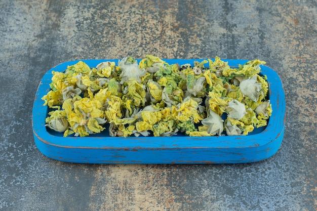 Pétalas de crisântemo secas na placa azul.