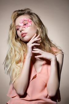 Pétalas de flores. modelo tenro com pétalas de flores ao redor dos olhos, uma sensação incrível ao trabalhar com o fotógrafo
