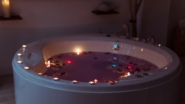 Pétalas de flores na banheira de hidromassagem com água violeta e velas acesas nas bordas