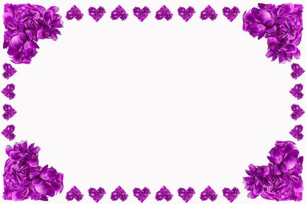 Pétalas de flores roxas em forma de coração na superfície branca