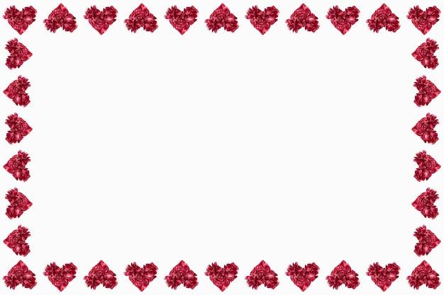 Pétalas de flores vermelhas em forma de coração na superfície branca