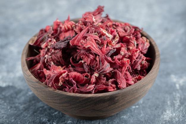 Pétalas de hibisco secas em uma tigela de madeira.