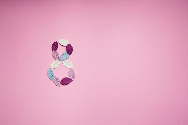Pétalas de papel multicolorido em forma de um oito em um fundo rosa.