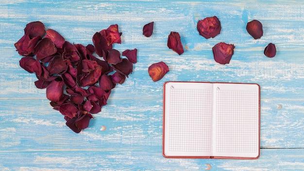 Pétalas de rosa em forma de coração na mesa de madeira vintage.