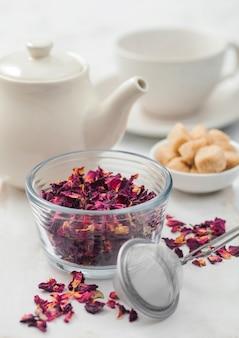 Pétalas de rosa orgânicas frescas com infusor de peneira e bule de cerâmica branca e açúcar de cana em fundo branco.