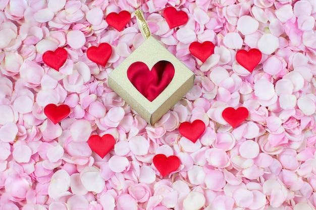 Pétalas de rosa rosa, corações de cetim e uma caixa de presente