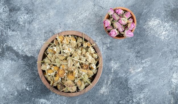 Pétalas de rosa secas e camomilas em tigelas de madeira.